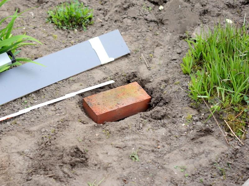 Als erstes werden die Eckpunkte für das Hochbeet ausgemessen und Pflastersteine als Fundament für die Eckpfosten gesetzt