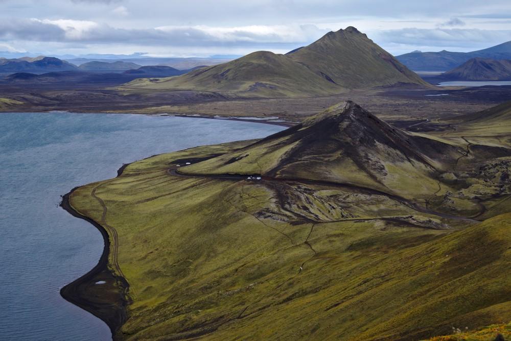 Wandern in Landmannalaugar - die Landschaft verändert sich hinter jedem Hügel, mal ist sie schroff und Lavaschwarz, mal grellgrün, manchmal leuchten die Berge in allen Farben. Die Anfahrt per Bus über Schotterstraßen und durch mehrere Furten lohnt sich.