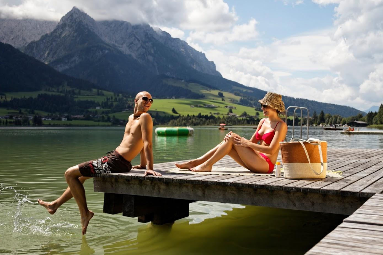 Walchsee mit zwei Badegästen, die auf einem Steg sitzen