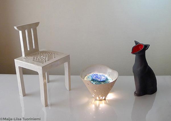 """Installation """"At the source"""" en trois pièces. Chaise mandala en céramique émaillée blanc ; récipient cônique en céramique émaillée sable, avec une plaque de verre fusionné coloré et un système d'éclairage LED ; récipient en forme de chat, émaillé noir mat"""