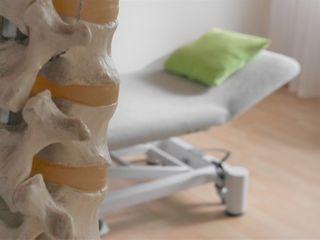 Wirbelsäule mit Bandscheiben vor Osteopathie-Behandlungsliege