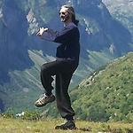 un homme pratique le taï chi dehors, en montagne, l'été