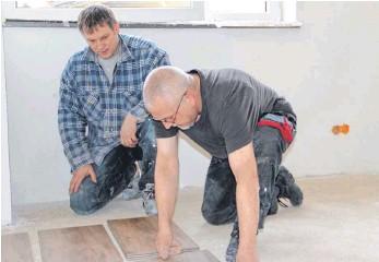 Frank Mehner (links) und Manfred Marx machen sich ans Fliesenlegen im neuen Feuerwehrhaus