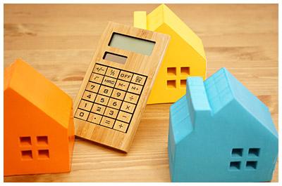 家の積み木と電卓のイメージ