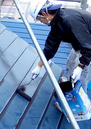 屋根塗装をしている職人の写真