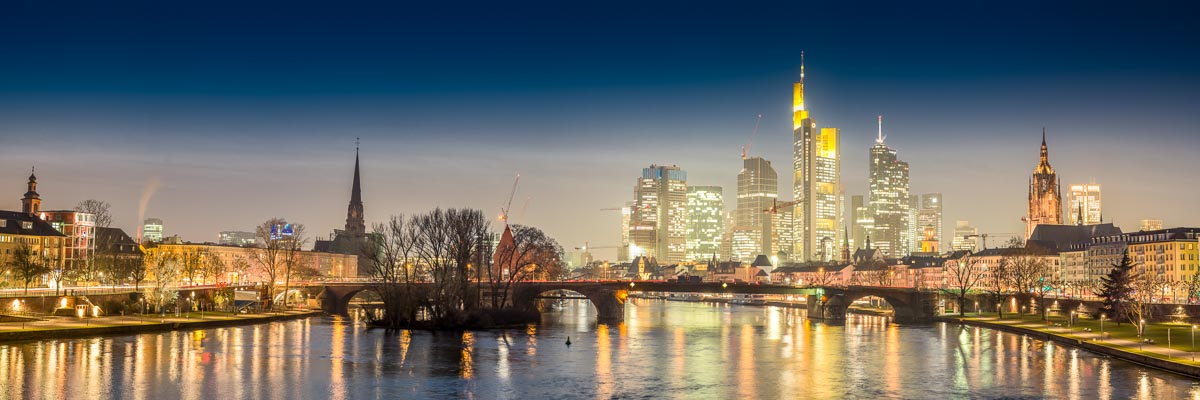 Die Skyline der Innenstadt von Frankfurt über dem Main hinweg zur blauen Stunde