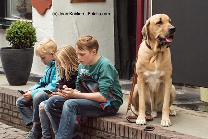 Trauriges Alltagsbild von Kindern: Alle zusammen, aber alle einsam mit ihrem Mobiltelefon. Nur der arme Hund langweilt sich.