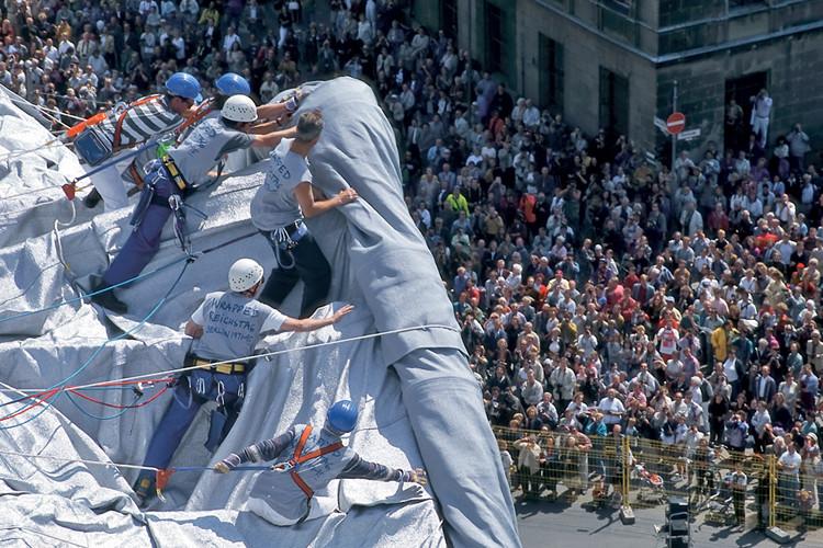 Eine der Dachmannschaften stößt eine Gewebebahn über die Giebelkante der Fassade. // Foto: Roland Bauer