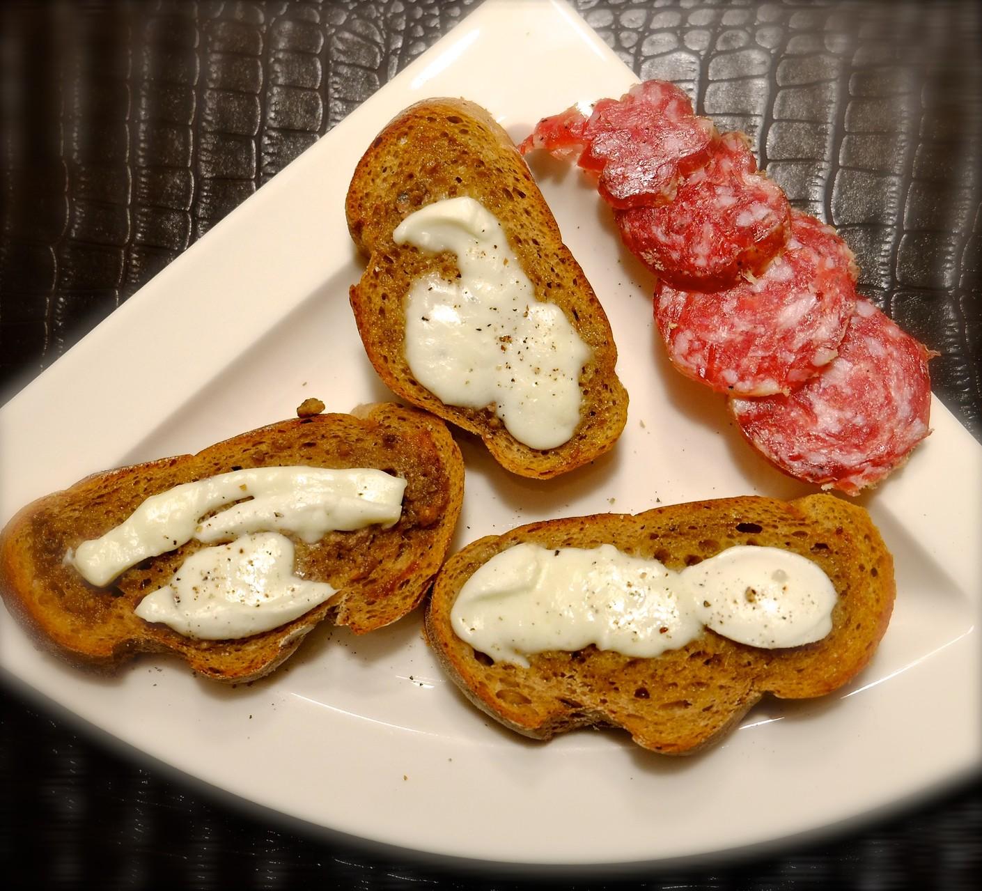 Zwischengang Roggen-Crostini mit Sardellen-Butter, Büffel-Mozarella + Trüffel-Salami