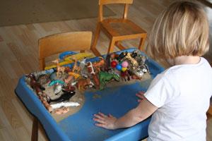 Kleinkind spielt mit beiden Händen im Sand mit Spielfiguren an einem Sandspieltisch