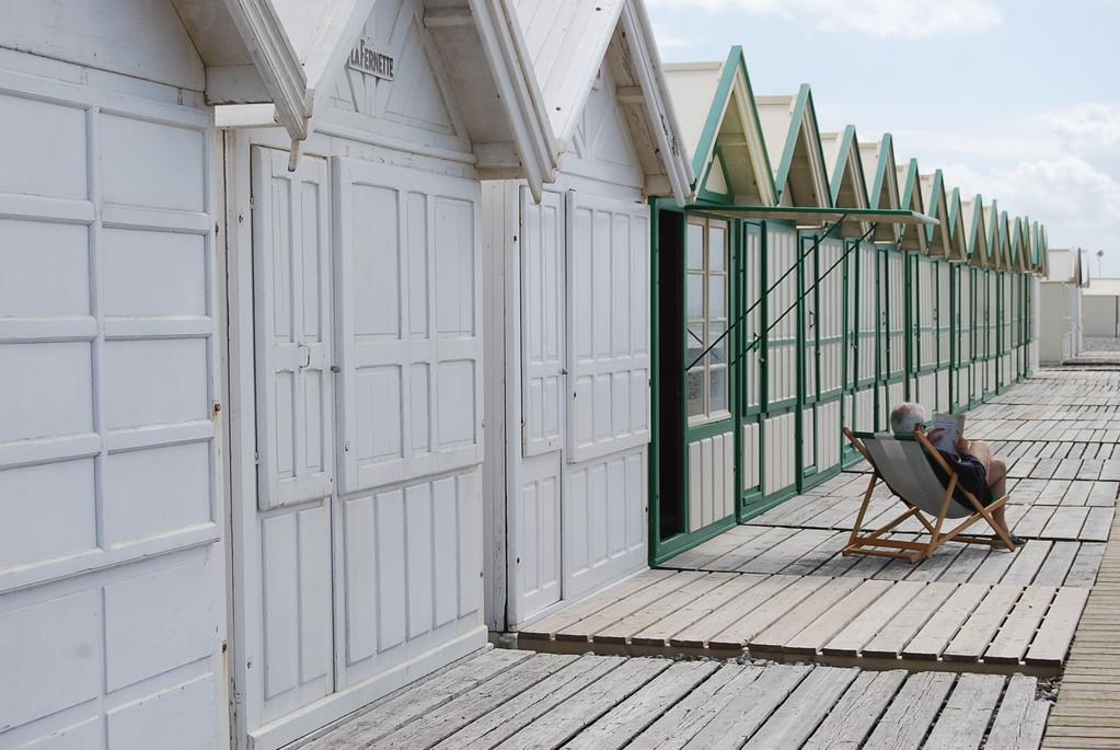 Le lecteur solitaire sur le chemin de planches à Cayeux sur mer