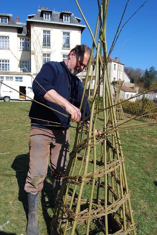 Pierre monte une pyramide devant l'école d'osiériculture