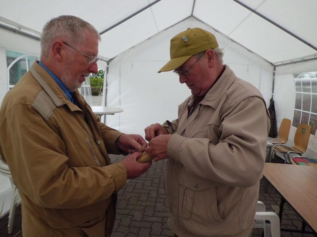 Günter Rockmann (li.) und Gebhard Edner stellen ein Bündel aus kleinen Schilfstücken zusammen, die mal als Brutröhren für Insekten dienen sollen