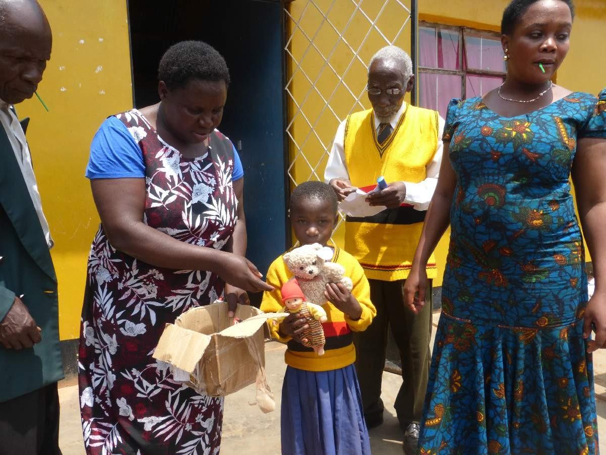 Einige Waisenkinder erhielten Weihnachtspäckchen von ihren deutschen Paten und zeigen stolz ihre kleinen Geschenke.