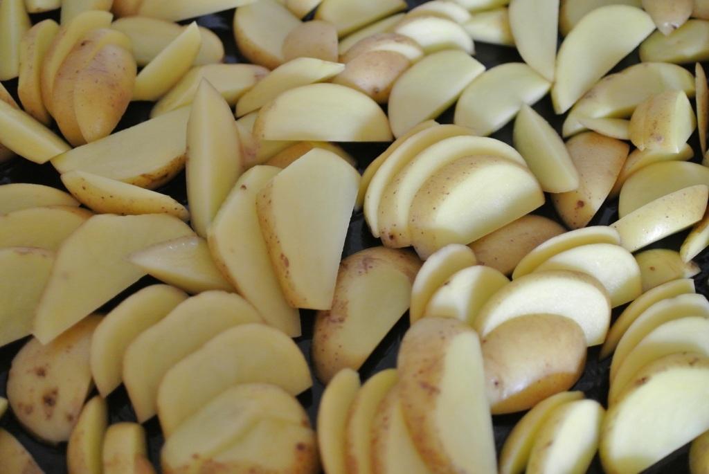 und in Scheiben (ca. 0,5 cm) schneiden. Backofen einschalten und die Kartoffelschnitze auf ein geöltes Backblech legen.