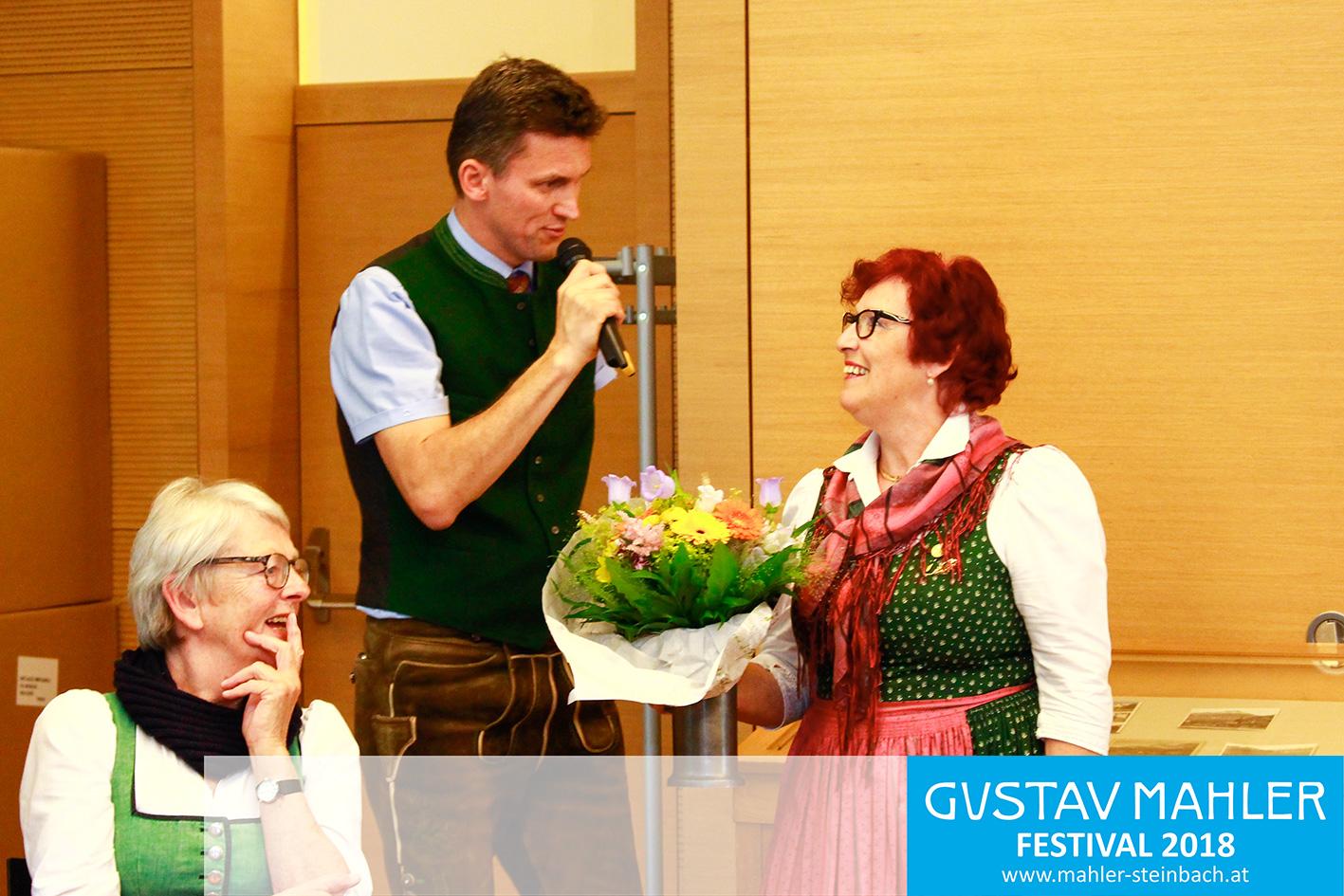 Georg Föttinger überreicht Kuratorin Roswitha Gebetsroither Blumen