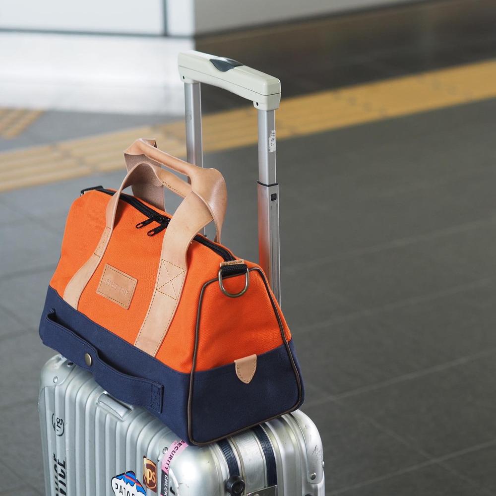 オレンジの旅行バッグ