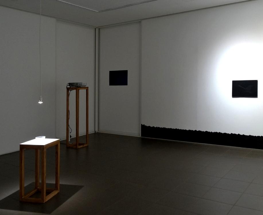 A gauche : Le noir se fait attendre, 2015, vidéo monocanal, son, 04:22 env. A droite : Au fond, 2016, fusain sur mur, dessin sur place, 320 x 300 cm. env