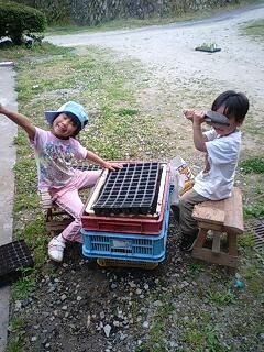 種まきをする娘と息子の写真