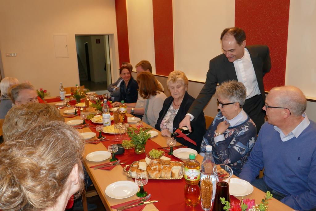 Pfarrer Schmitz schenkt bei der Agape-Feier den Wein ein