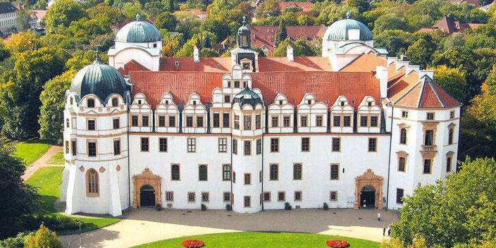 Schloss Celle aus der Vogelperspektive im Sommer. Schönes Barockschloss, quadratisch mit 3 patinierten Kuppeltürmen und rotem Pfannendach.