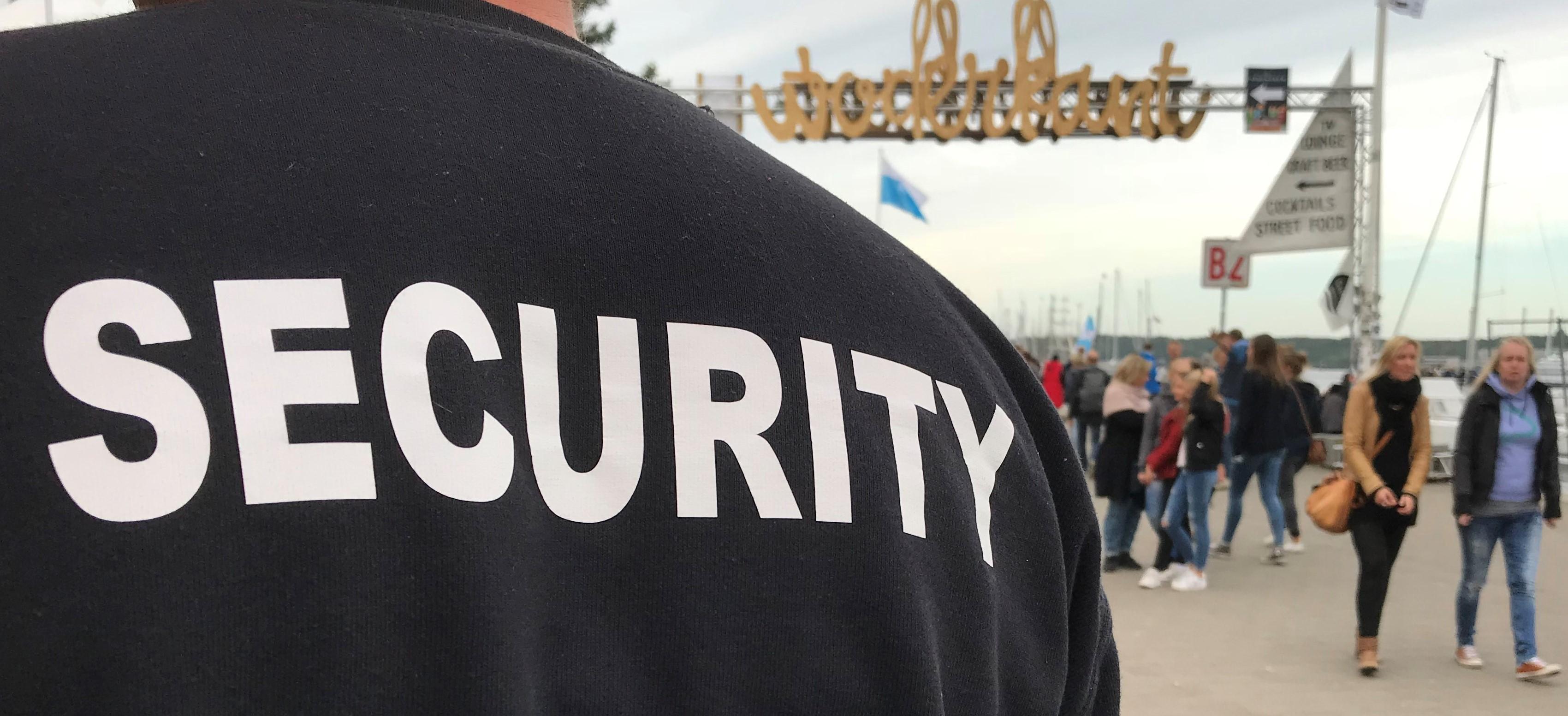 """Rücken eines Sicherheitsmitarbeiters im schwarzen Shirt mit """"SECURITY"""" in Großbuchstaben vor einem Durchgangstor bei der Kieler Woche. Auf dem Tor steht """"Waterkant"""" und Menschen laufen oder schlendern im Hintergrund umher."""