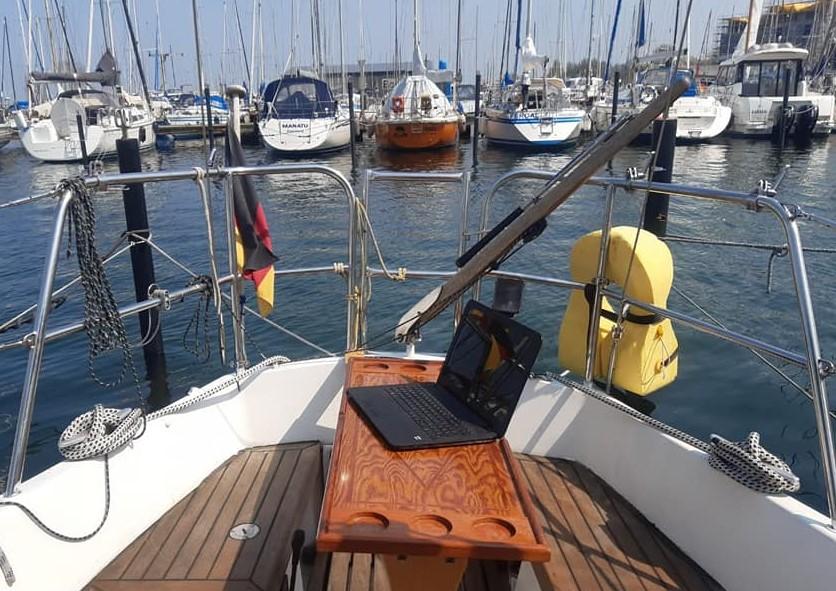 Das Heck eines Segelbootes mit Deutschlandfahne im Hafen. Auf der gegenüber liegenden Seite sind ca. 10 weitere Boote zu sehen, die im Hafen liegen. Auf einem Holztisch steht ein aufgeklappter Laptop.