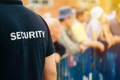 """Sicherheits-Mitarbeiter mit Schriftzug """"SECURITY""""auf dem Rücken vor Straßen-Absperrung, ggf. auch im Stadion oder bei einem Konzert."""