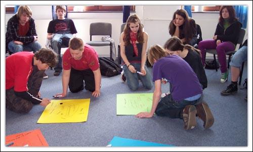 Teilnehmerinnen  und Teilnehmer knien auf dem Boden und gestalten ein Plakat