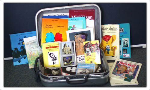 Ein aufgeklappter Koffer in dem verschiedenen Büchern enthalten sind