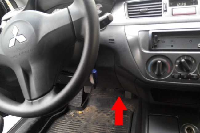 Red arrow indicates the place where there is a socket for the diagnosis of the vehicle Mitsubishi