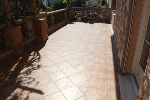 Terrrasse carrelée avec deux tapis en diagonale