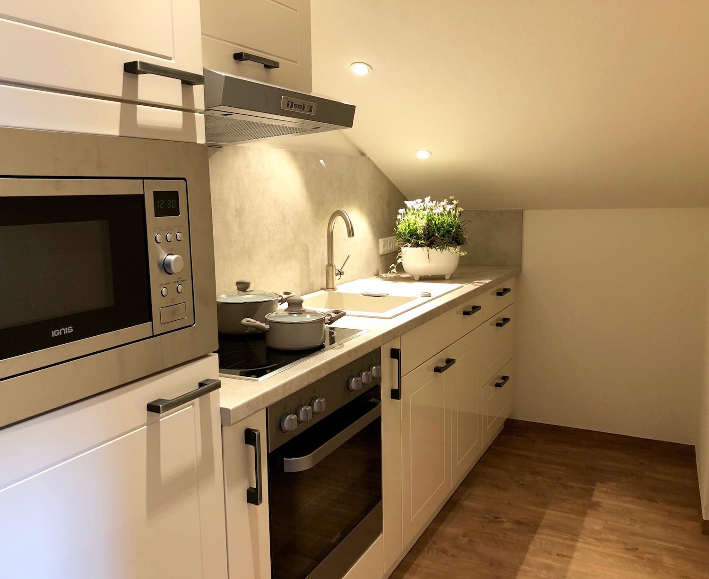 Separate Küche mit 4-Platten-Herd, Backofen, Spülmaschine u. Mikrowelle.