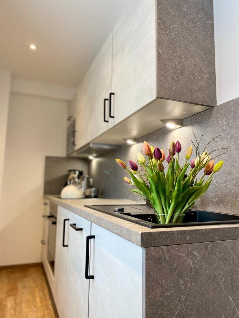 Separate Küche mit Ceranfeld, Backofen, Spülmaschine u. Mikrowelle.
