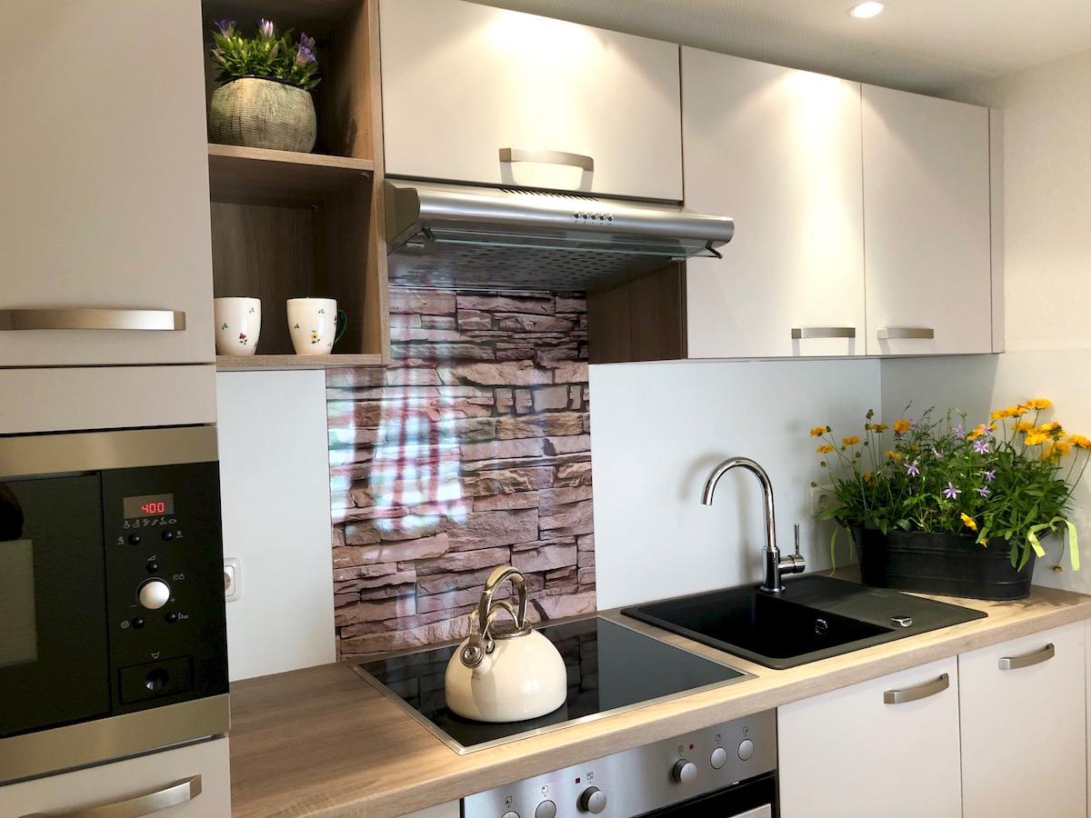 Komfort-Küche mit Ceran-Kochfeld, Backofen, Geschirrspüler und Mikrowelle.
