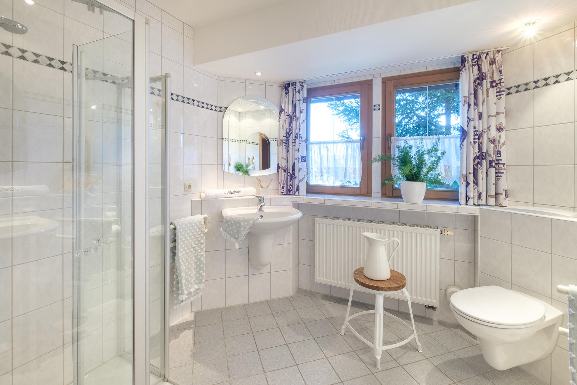Badezimmer mit 2 separaten Waschbecken, bodenbündiger Dusche sowie viel Tageslicht.