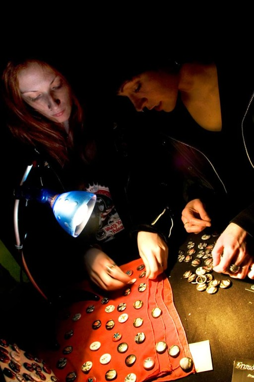 Cristina, on the left, and Delphine, on the right, while they are preparing punk-hardcore label bedges to sell during a Hardcore concert in squatted center 'Villaggio Globale'. 2008