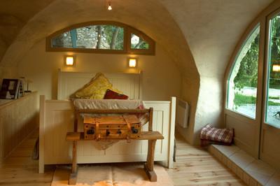 Une chambre voûtée pour deux personnes avec douche, lavabo et toilette en-suite.