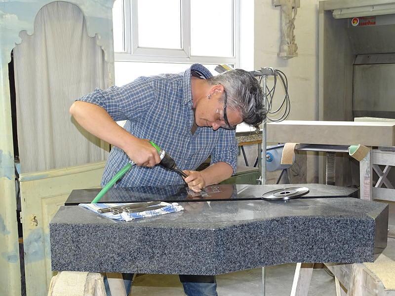 Stephanie Grießhaber vom Steinmetzbetrieb Erinnerungen in Stein aus Pfullendorf beim Einarbeiten einer Schrift in einen Grabstein