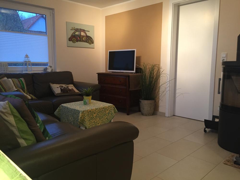 Offener Wohnbereich mit Smart-TV und Kaminofen