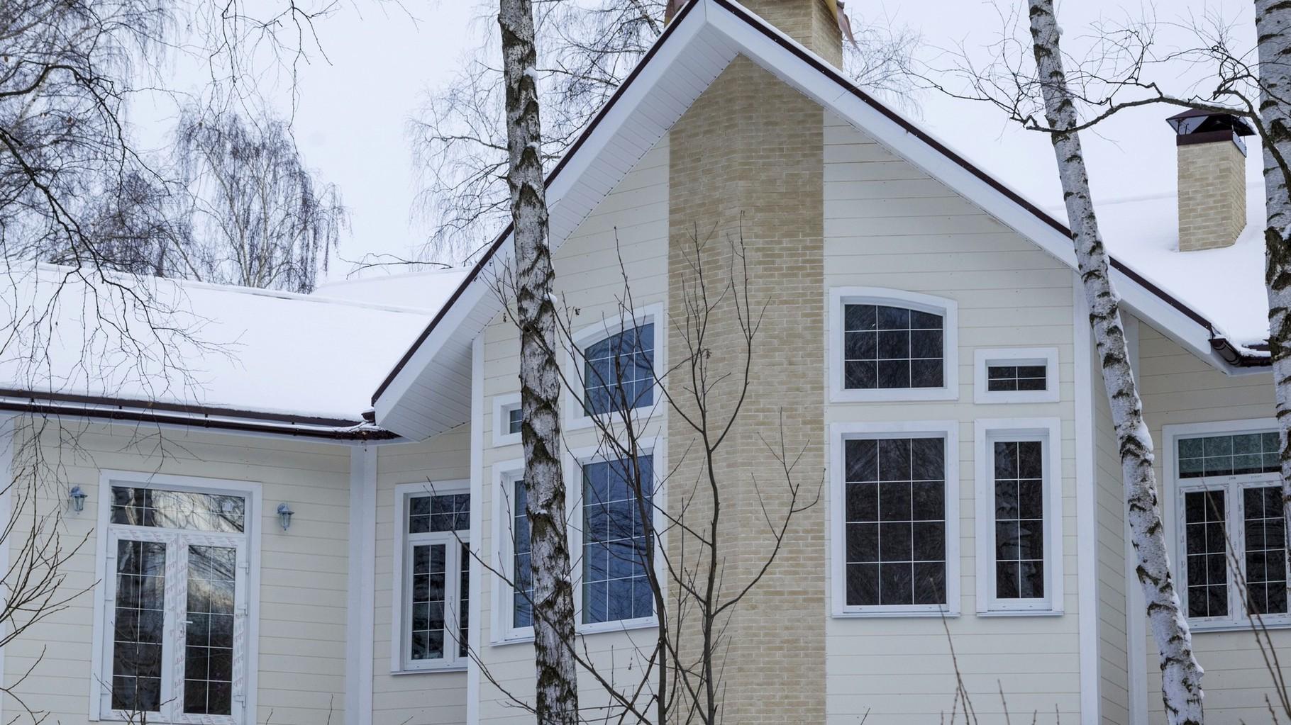 Обшивка фасада - раухаус. Наличники - деревянные. Декоративные детали - искусственный камень.