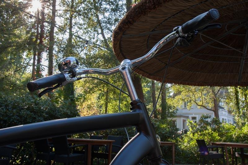 """Foto : Andreas Hartwig, Bild zeigt einen Fahrradlenker unter einem Sonnenschirm vor dem Graftwerk  in den Delmenhorster Graftanlagen, Fahrrad von Zweirad-Kehlenbeck, Delmenhorst, Bildstrecke """"unterwegs in Delmenhorst"""""""