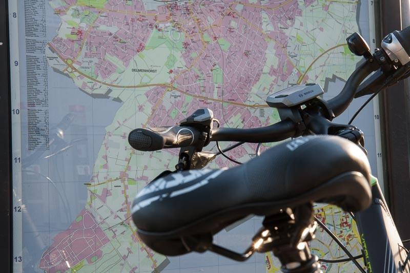 """Foto: Andreas Hartwig, Bild zeigt ein Fahrrad von Zweirad Kehlenbeck vor einem Delmenhorster Stadtplan auf dem Bahnhofsvorplatz in Delmenhorst, Bildstrecke """"unterwegs in Delmenhorst"""""""