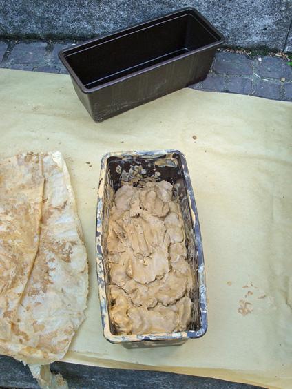 In Formen gefüllter Ton, der anschließend mit Löchern versehen werden wird.