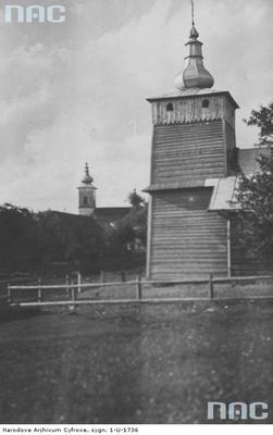 Izby - prawosławna cerkiew drewniana, w tle widoczna wieża cerkwi św. Łukasza. Zdjęcie pochodzi ze zbiorów Narodowego Archiwum Cyfrowego