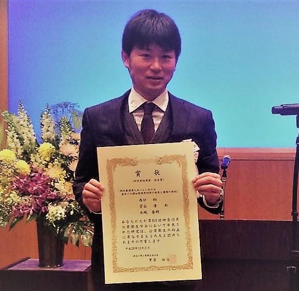 研究奨励表彰状をもち笑顔を見せる西口先生