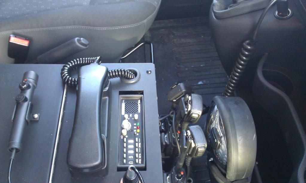 Multifunktionskasten. Von links nach rechts: Mikrofon für Lautsprecherdurchsagen; Hörer 4m Funkgerät; 4m Funkgerät; 2m Handsprechfunkgeräte Motorolla GP 360 (4 Stück) in den Ladeerhaltungen und der Suchscheinwerfer.