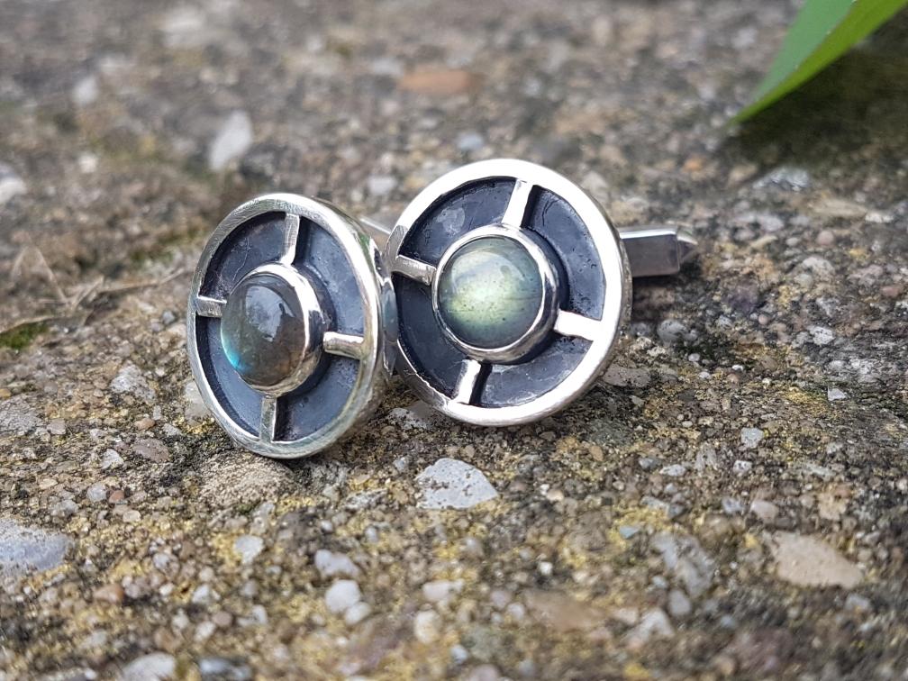 Zilveren manchetknopen met labradoriet. Een eerdte ontwerp waarin een gelaagdheid is toegepast. De diepere delen zijn donker gemaakt voor extra contrast met de randen en de steen.