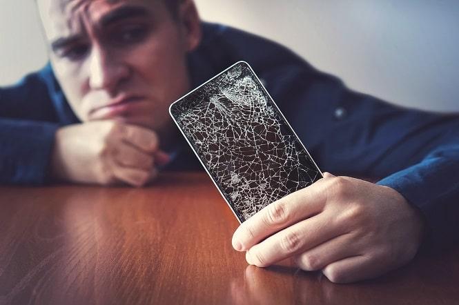 Mann hält  Smartphone mit gebrochenem Display
