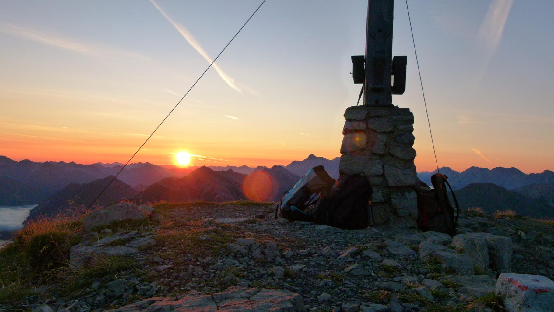 Wunderbarer Blick mit der Sonne hinter dem Gipfelkreuz